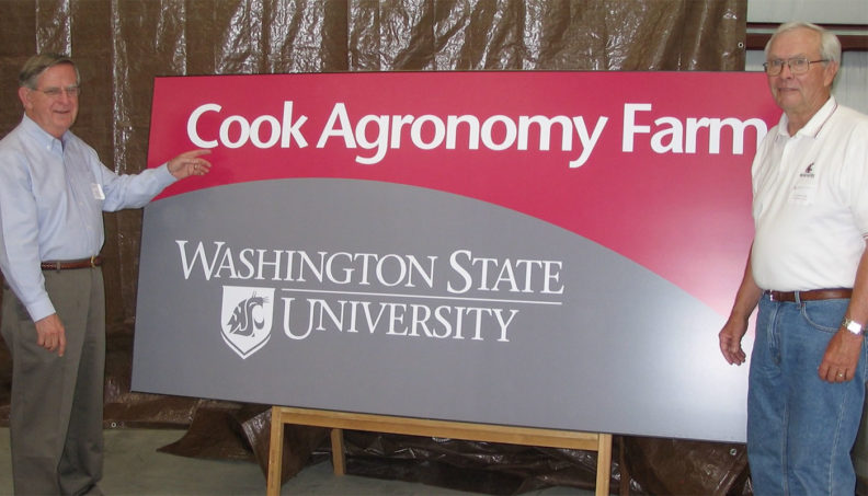 Jim Cook and Sam Smith next to WSU Cook Agronomy Farm sign