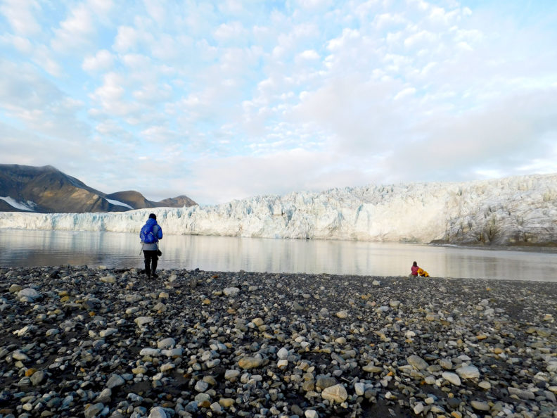 Standing on rocky shore of Svalbard, person looks at a glacier. Photo Debbie Lee