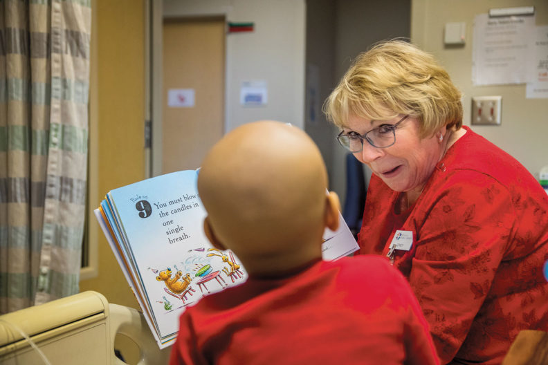 Spokane librarian Cindy Wigen reads to a young patient at Sacred Heart Hospital