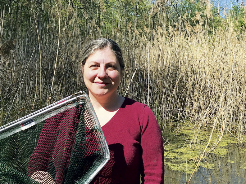 Erica Crespi with a net by a pond
