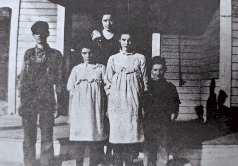 Four children and teacher stand in front of Riviera School circa 1917