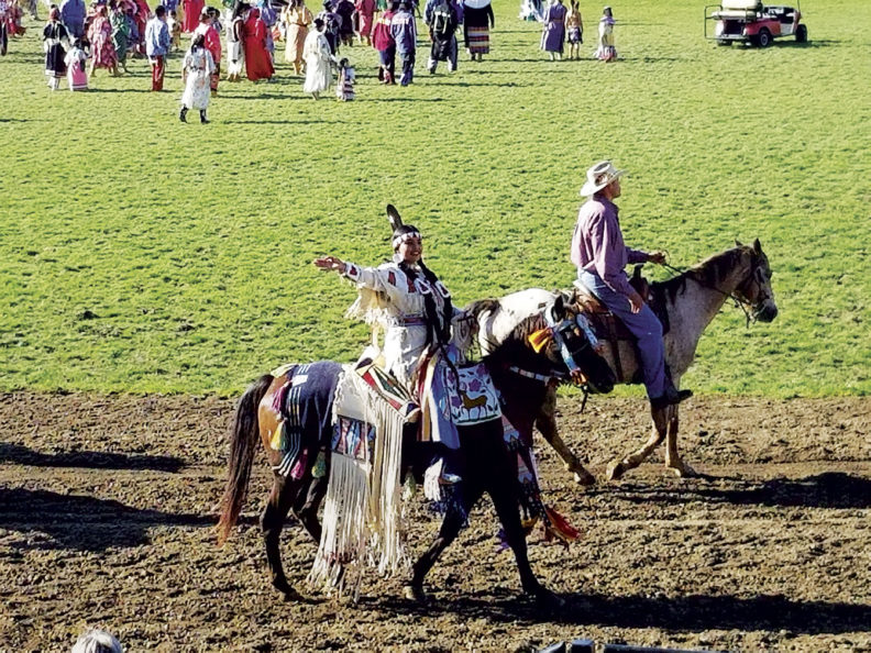 Participants ride horses in the Round-Up Native American Parade