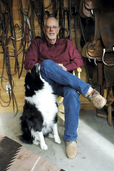 Don Weller seated with his dog at home in front of bridles and saddles