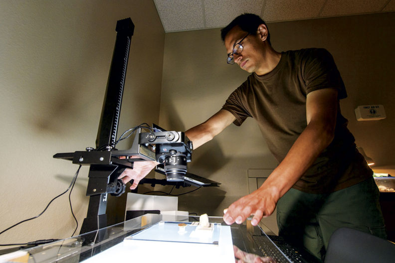 WSU student and veteran Trent Raymer takes photos of artifacts