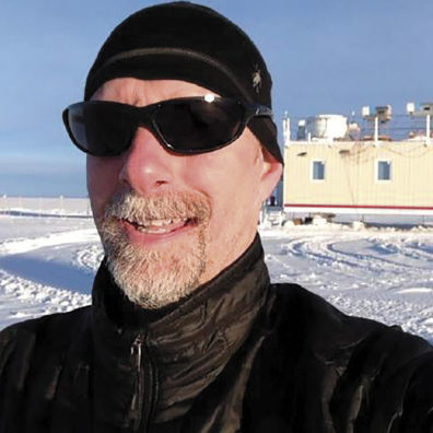 Von Walden wearing sunglasses in front of his mobile laboratory in Greenland