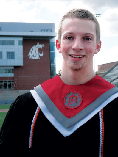 Jonathon Waldrip with WSU graduation robes at Pullman campus