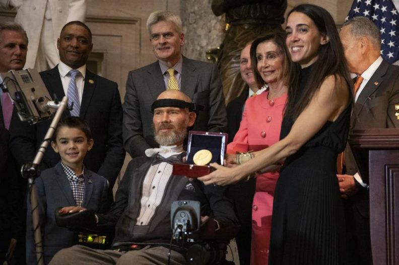 Steve Gleason receives the Congressional Gold Medal surrounded by his family, House Speaker Nancy Pelosi, and other members of Congress