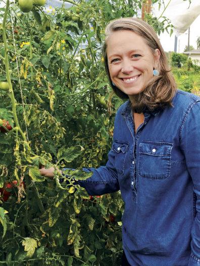Jordan Jobe shows a tomato plant at a farm
