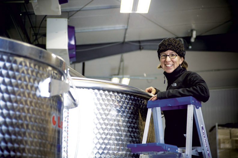 Coco Umiker examines a wine making tank