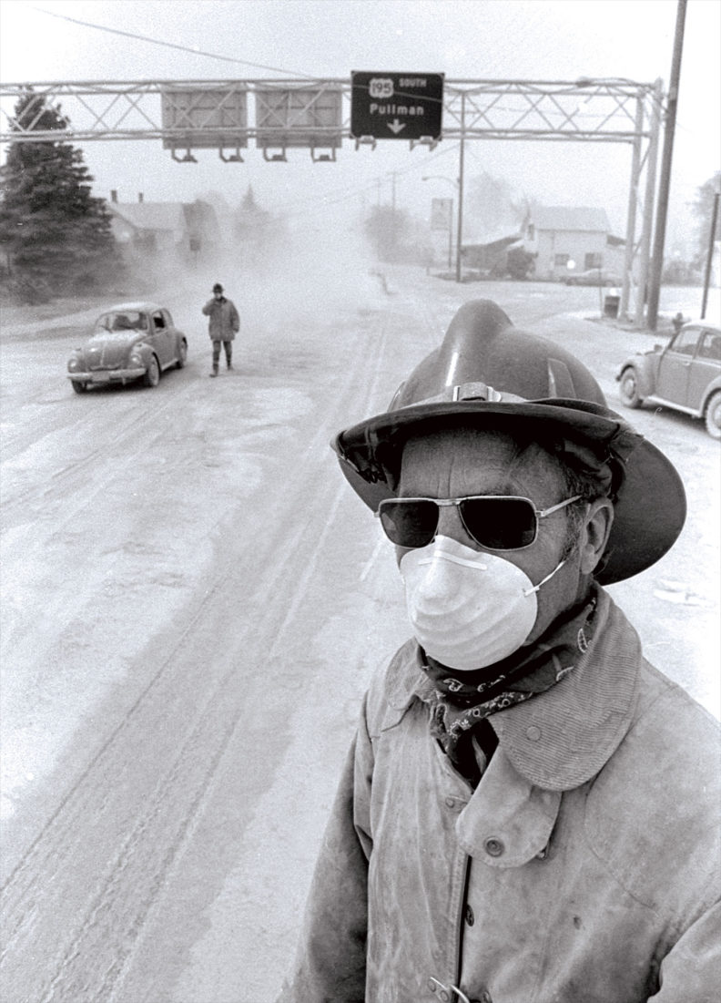 Colfax, Washington, firefighter wearing facemask next to US Highway 195