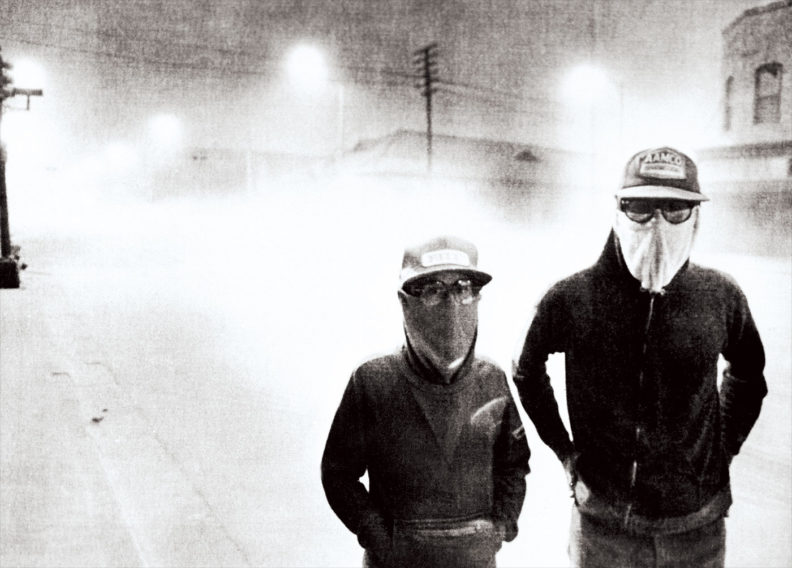 Two people in facemasks walk on a dark street in Yakima after ash from Mount St. Helens eruption in 1980