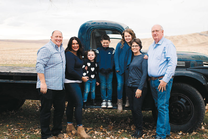 Mader family of Palouse Brand by old truck in a field