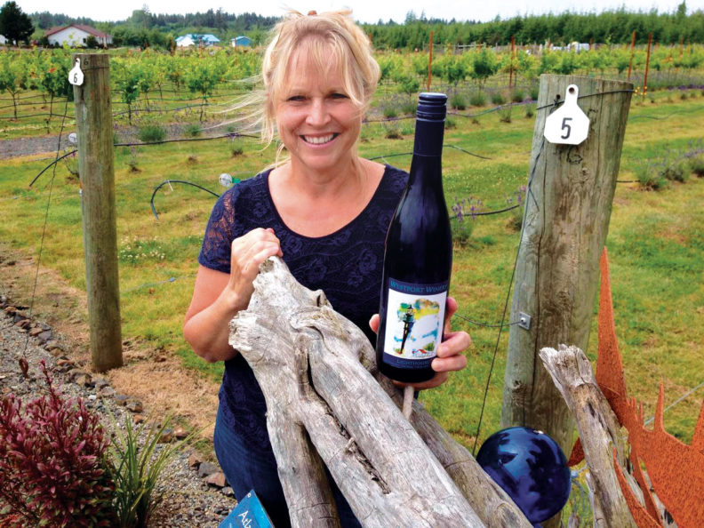 Kim Roberts from Westport Winery stands in front of the vineyard with a bottle