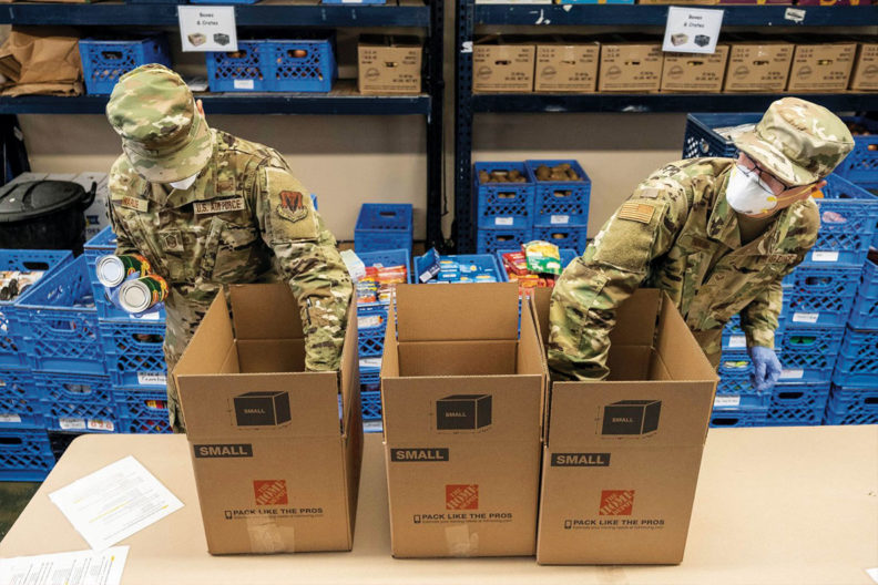 Two Air National Guard members get canned goods from box for food bank