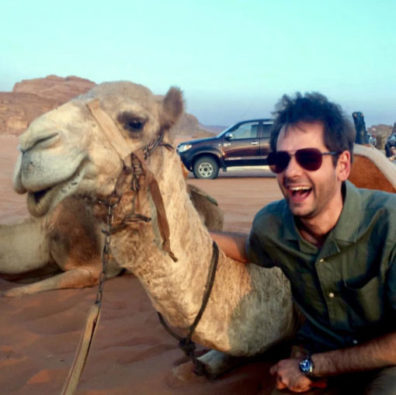 Michael Letko sits next to a camel