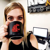 Taryn Daly drinks coffee from her WSU Coug head mug in front of radio equipment
