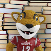 Butch Cougar in front of a pile of books