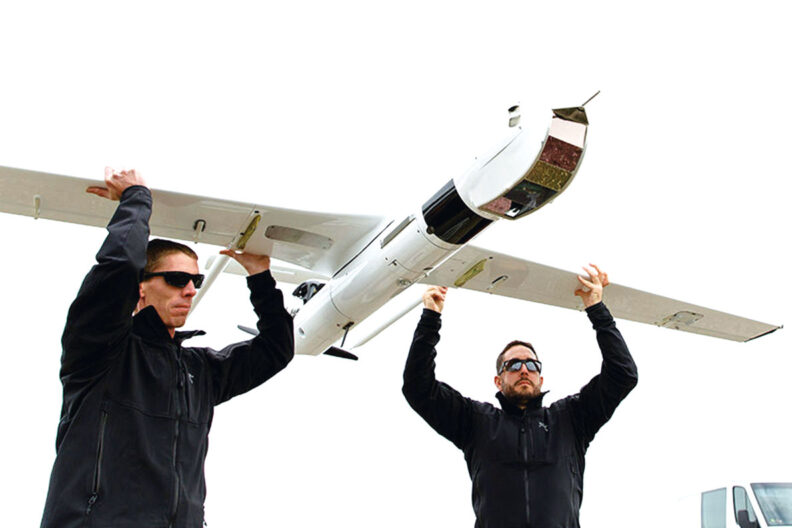 Two men hold up a drone that uses hydrogen fuel