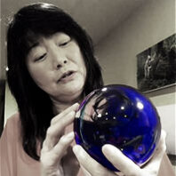 Artist Etsuko Ichikawa with a blue glass orb she made for exhibit