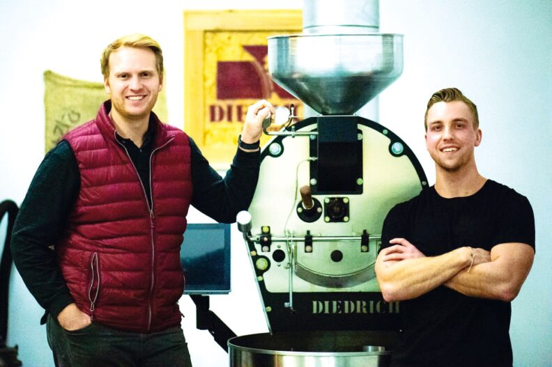 Kyle O'Malley and Grant Schoenlein next to grinder at Kamiak Coffee