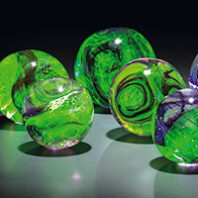 Blue and green glass orbs in art exhibit Broken Poems of Fireflies by Etsuko Ichikawa