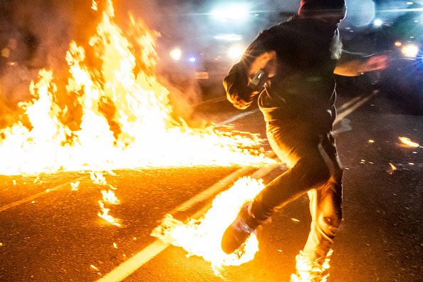 A protestor with a burning foot from a Molotov cocktail during the 2020 Black Lives Matter protests in Portland, Oregon