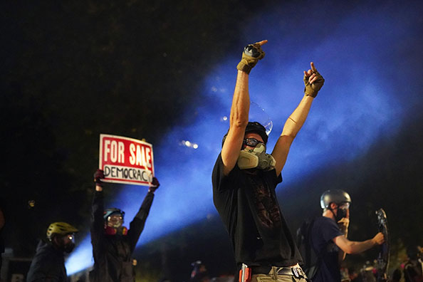 Protestor flips off police as tear gas is fired during the 2020 Black Lives Matter protests in Portland, Oregon.