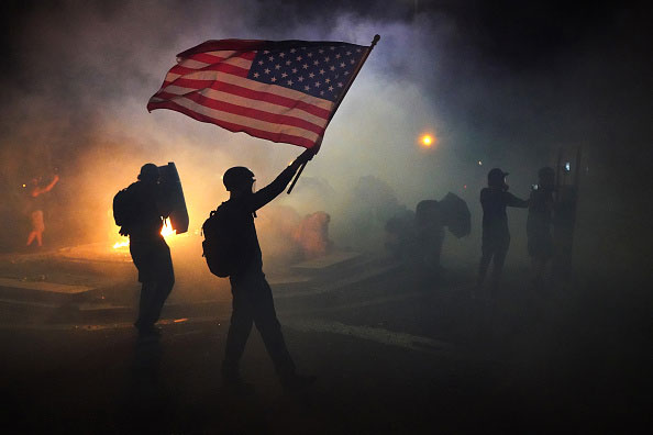 Protestor waves an American flag in the smoke during the 2020 Black Lives Matter protests in Portland, Oregon.
