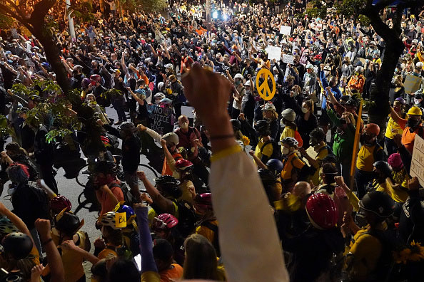 Thousands of marchers during the 2020 Black Lives Matter protests in Portland, Oregon. A raised fist in the foreground