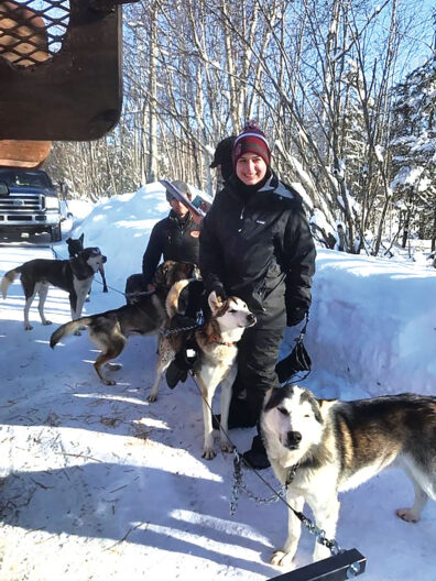 Laura White with sled dogs at the 2020 Iditarod Race