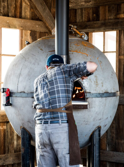 Removing bread from buoy oven at WSU Bread Lab