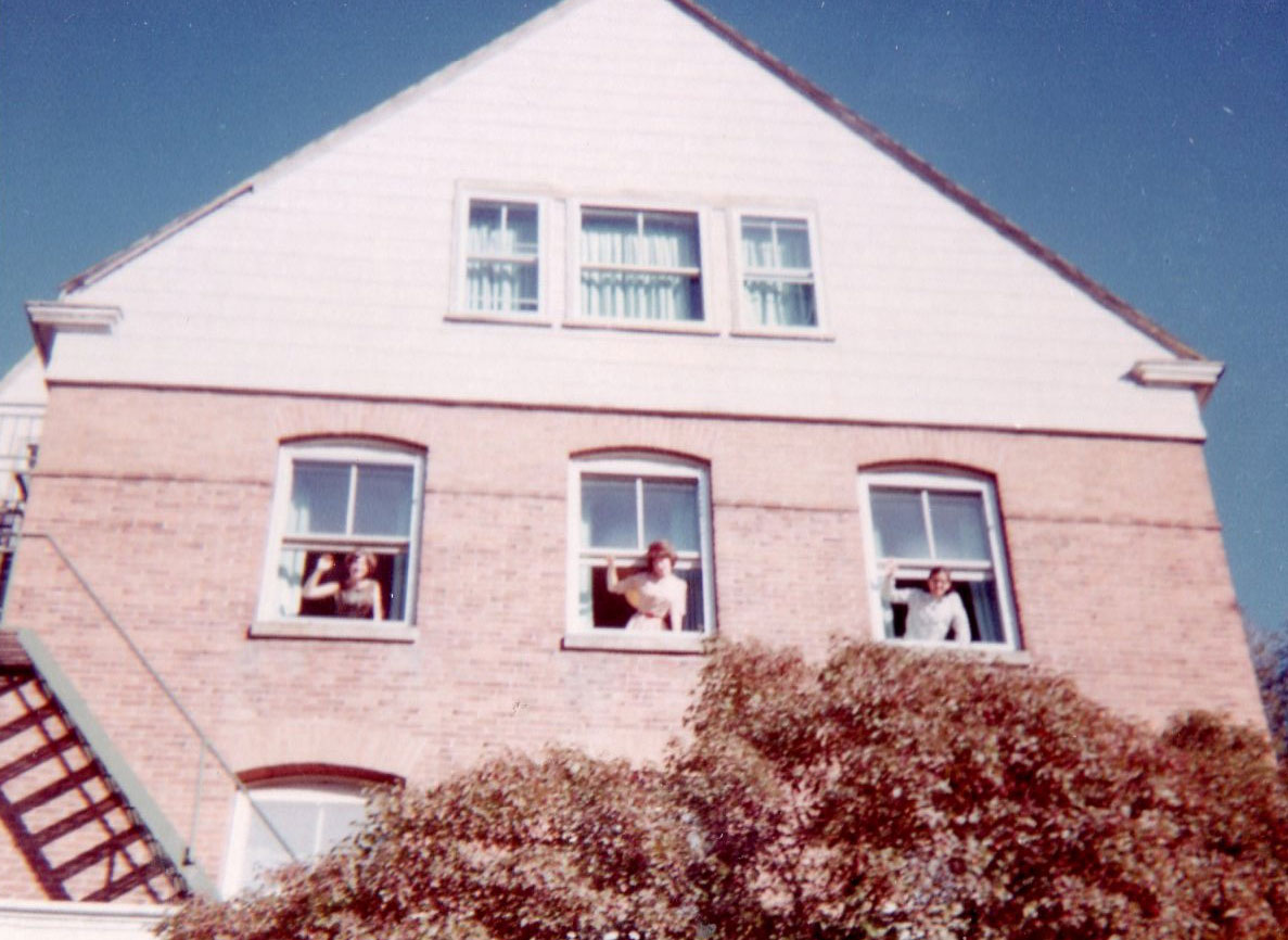 Stevens Hall 1964 with three women waving from windows
