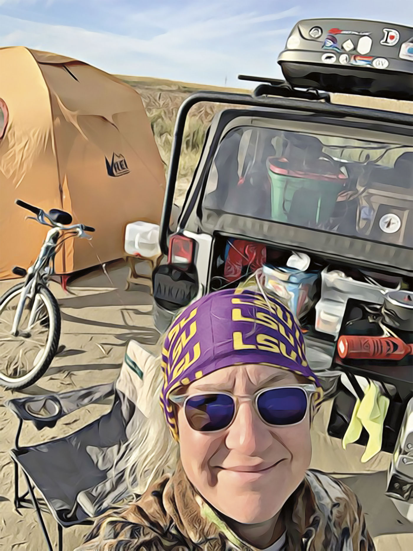 Michelle in front of her jeep, bike, and tent