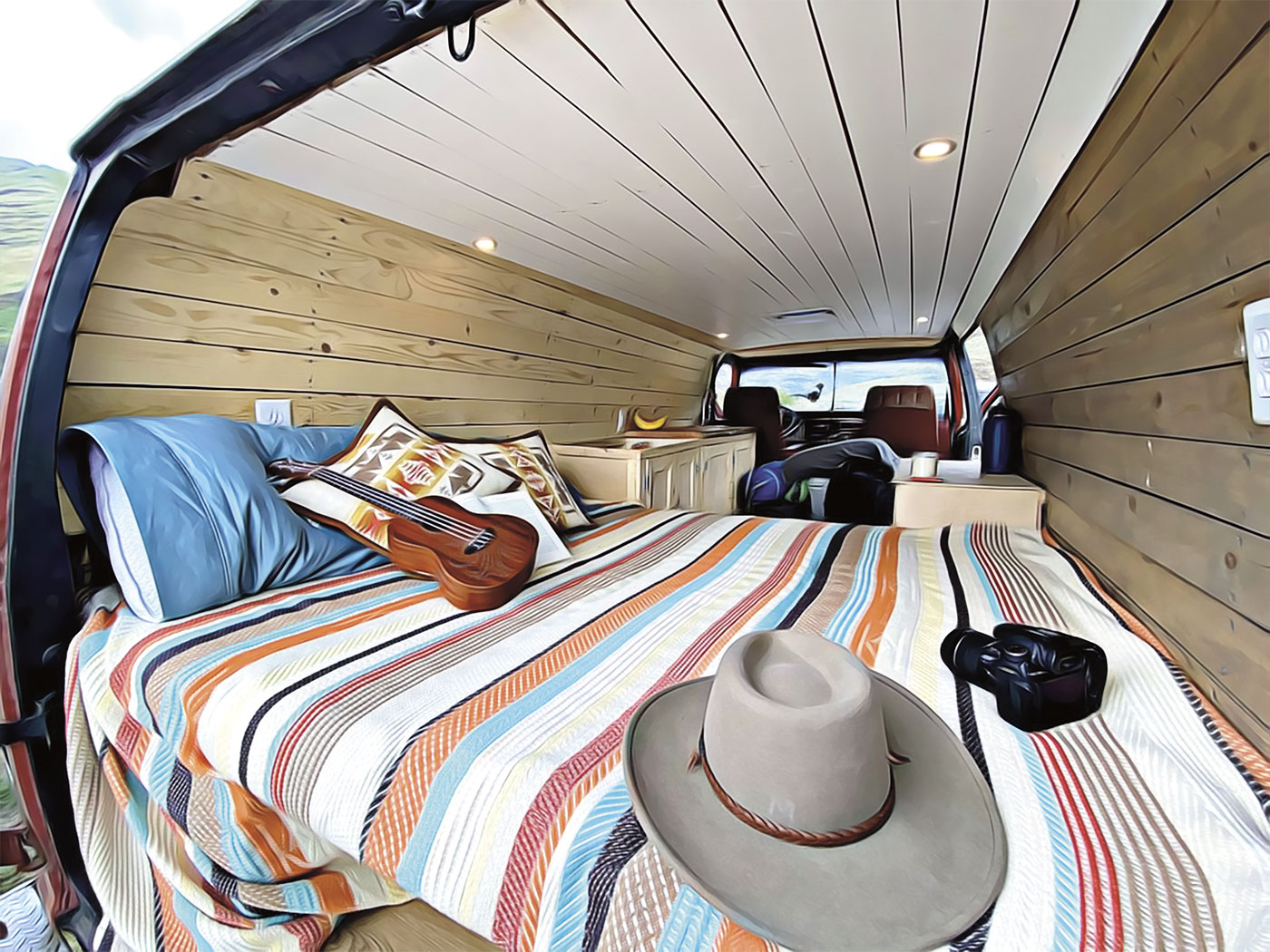 Inside of Dalton Russell's renovated van with bed, guitar, sink
