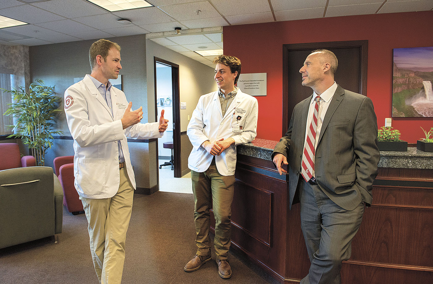 WSU Elson S. Floyd College of Medicine Dean John Tomkowiak talks with medical doctor students Alex Franke and Ryan de Leon