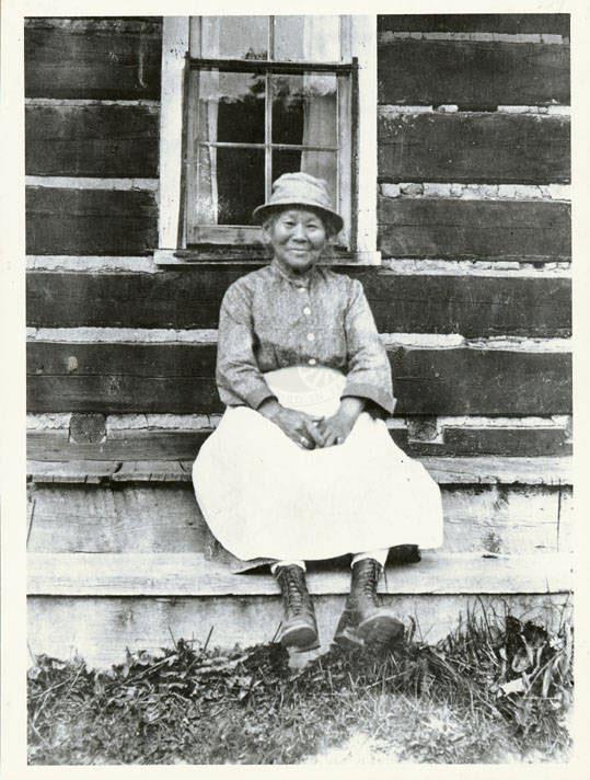 Polly Bemis sitting outside a cabin in Warren, Idaho
