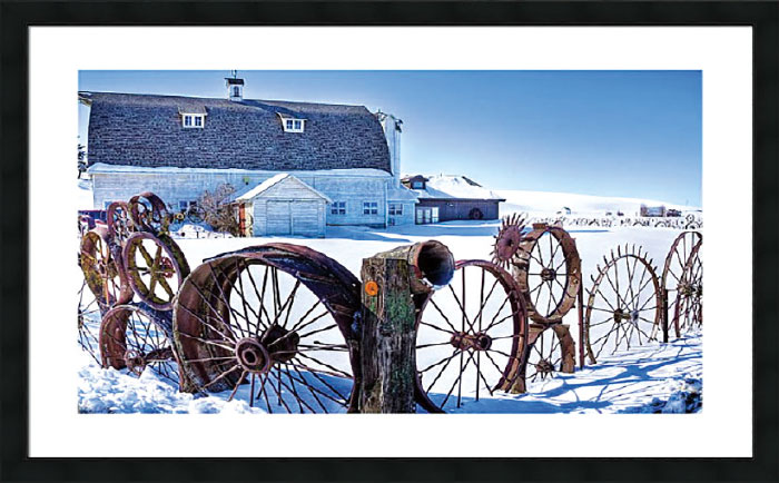 Photo of fence made of old metal wheels in front of a barn in snow