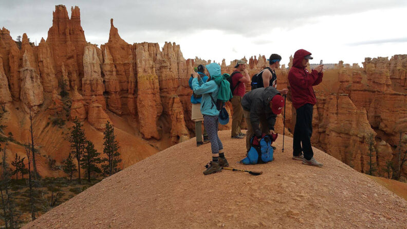 A tour group takes photos in Zion National Park