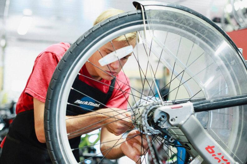 Young man repairs a bike