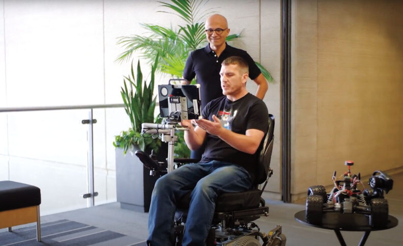 Jon Campbell sits in a wheelchair operated by eye-control. Microsoft CEO Satya Nadella stands behind watching.