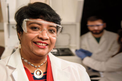 Researchers Susmita Bose in safety goggles and lab coat in her laboratory