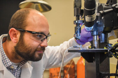 Researcher Arda Gozen looks at a 3D printer as he studies printed cartilage