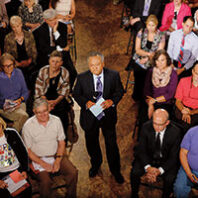 Journalist Enrique Cerna with a microphone and note cards among seated people at a Yakima town hall