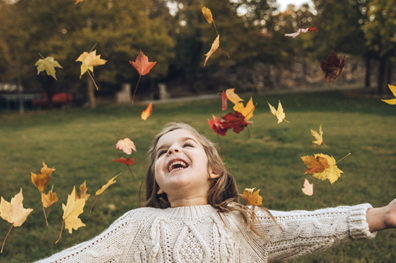 Girl throwing fall leaves into the air