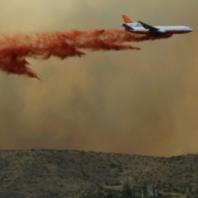 Airplane emitting red fumes while flying through air