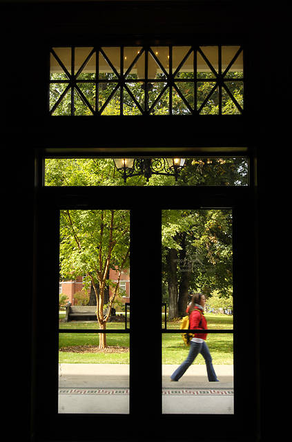 glass doors with a student passing by