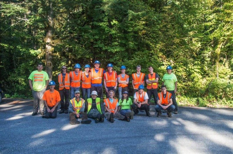 Group of men and women wearing safety gear in front of trees